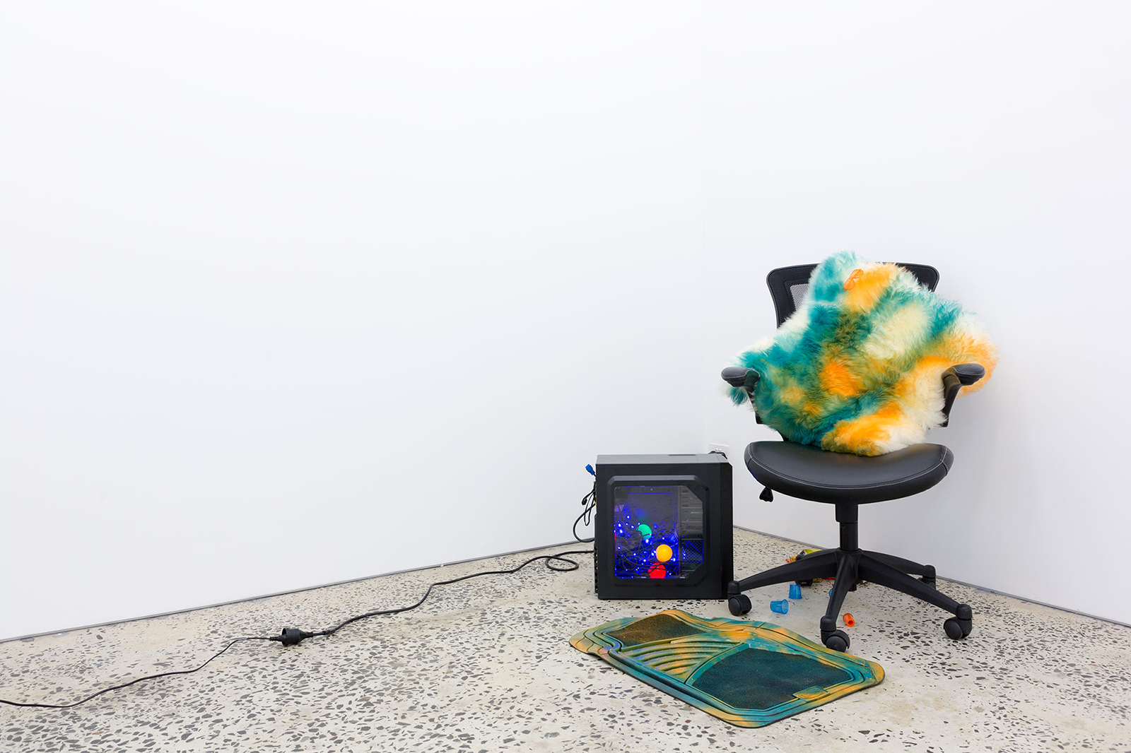 Contemporary Monsters, 2016, two-channel digital video, jelly shot glasses, gel wax, car air freshener, sheepskin, enamel paint, cereal, rubber mat, LED lights, computer tower, 11 minutes, 19 seconds